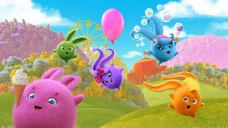 Round, fluffy characters in different colours jumping across a green field with a blue sky in the background.