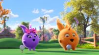 An animated image of two, round fluffy creatures on a golf course. One is purple with a pink bow, the other is orange.