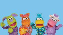 Four cute puppets dressed in colourful pyjamas waving and smiling in front of a light blue background,