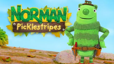 A friendly, green-striped creature wearing a tool belt is standing on a wooden log with his hands on his hips.