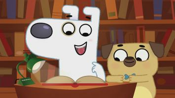 A friendly, white dog and a beige pug reading a book with a large bookshelf behind them.