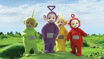 Green, purple, yellow and red plush characters standing in the middle of a green field and a blue sky in the background.