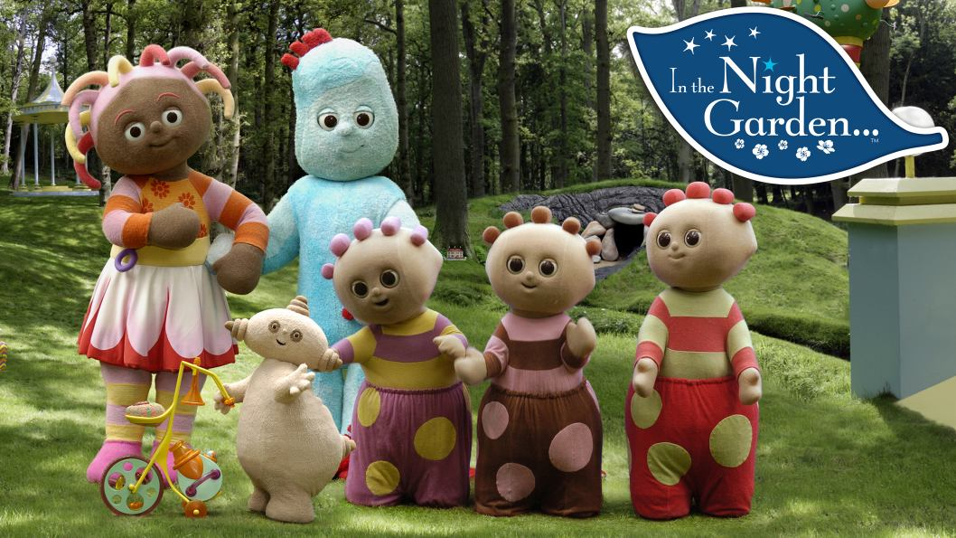 Six plush characters standing in a park.